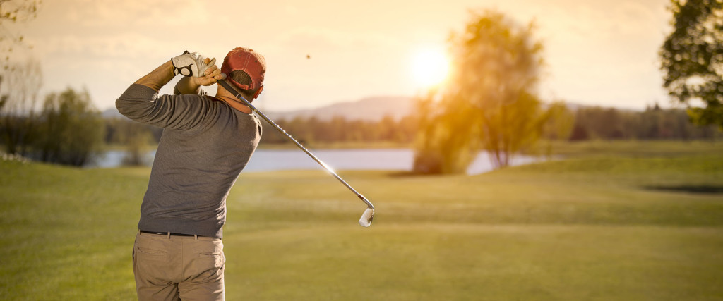 Male golf player swinging club at beautiful sunset in background