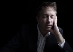 Portrait of businessman closing eyes while working late at night on black background with copy space